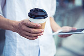 Man using tablet and holding coffee