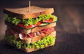 Delicious sandwich with ham, cheese, bacon and lettuce