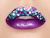 Close up view of beautiful woman lips with purple lipstick