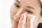 Women are doing skin care using cotton.