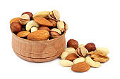 mix almonds, cashew nuts, hazelnut, peanuts, walnuts, pistachio in wooden bowl isolated on white background