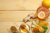 healthy background. honey, honeycomb, lemon, tea, ginger on white wooden table. Top view with copy space