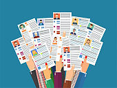 Hands holding cv resume documents.