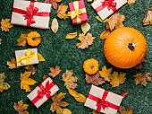 various autumn leaves and orange pumpkins with gifts