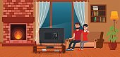 Young couple sitting on sofa watching TV by fireplace.