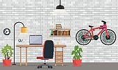Interior of office or room with white brick wall. Modern room for work and leisure with a table, a laptop, chair, lamp lighting, shelf with books, bicycles.