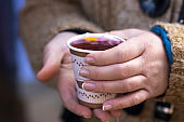 Paper tea machine in female hands when it's cold