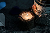 white candle with dark background - in a wooden candlestick
