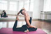 Young pretty flexible woman coach is doing yoga sports