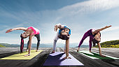 Young beautiful women and man practicing outdoors yoga