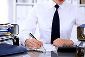 Close up of business woman making report, calculating or checking balance.