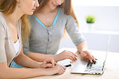 Two friends or sisters making online shopping by credit card. Friendship, family business or internet surfing concept