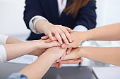 Unknown business people joining hands, close-up. Teamwork concept