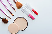 Make up and cosmetic beauty products arranged on a light purple background, with empty space at side'n