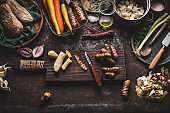 Jerusalem artichoke peeling preparation on rustic kitchen table with pot, diced vegetables, oil and ingredients, top view.