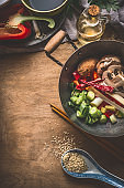Wok pot with vegetarian asian cuisine ingredients for stir fry with chopped vegetables, spices, sesame seeds and chopsticks on rustic wooden background, top view.