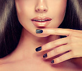 Peach color lipstick and black manicure.