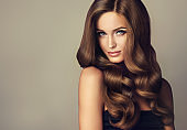 Young, brown haired beautiful model with long, wavy,well groomed hair.