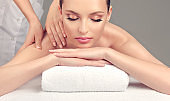 Tender and soft hands of massage specialist is making massage on the back of young woman.
