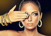 Golden make up, bright gilded manicure and elegant gesture. Portrait of attractive woman model in golden color..