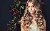Young, blonde haired beautiful model with long, wavy,well groomed hair. Stylish, loose hairstyle with freely lying curls.