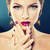Bright stylish make up and manicure in a purple and violet colores.