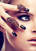 Beautiful woman in a smoky-eyes style make up and black manicure.