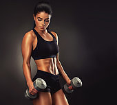 Athletic woman is pumping up muscles with dumbbells.