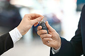 Close-up image of the car salesman hand giving a key to new owner