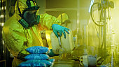 In the Underground Drug Laboratory Clandestine Chemists Wearing Protective Masks and Coveralls Mix Chemicals. One Pours Liquid From Canister into Bowl, Second Checks Beaker for Product Consistency. They Work in the Abandoned Building.