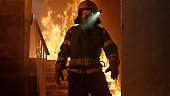 Brave Firefighter With Switched On Flashlight on His Helmet Standin Alone in Burning Staircase. Open Fire in the Background.