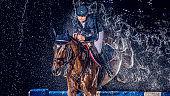Horse rider jumping through a water curtain