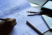 Divider, pencil, pen, ruler, glasses and smartphone and blueprint on table top.Table top view of Engineers table at office workplace.selective focus.Man hand editing blueprint.