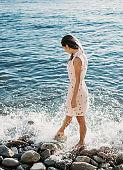 Beautiful woman walking on pebble beach.