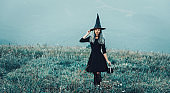 Witch walking in Halloween evening.