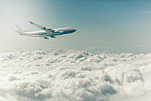 commercial airplane flying over the clouds