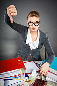 Dissatisfied young businesswoman with thumb down gesture.