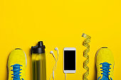 Flat lay shot of Sport equipment. Sneakers, water, earphones and phone on yellow background. Focus is only on the sneakers