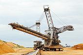 coal mining. Giant wheel of bucket wheel excavator. Long conveyor belt transporting ore
