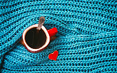 Turquoise knitted woolen scarf, red mug with coffee, heart