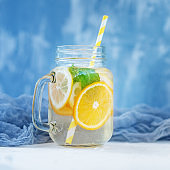Refreshing fruit water in a glass jar. Lemon, orange and mint. The concept is summer, diet, vegetarian, fitness, healthy eating and lifestyle.