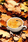 'Abstract background with  autumn leaves and hot coffee cup. Yellow Fallen autumn leaves
