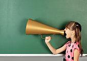 child shouting magaphone near blank school blackboard, copy space