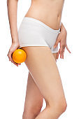 Midsection of slim latin woman holding an orange