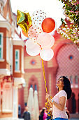 beautiful young woman with air balloons on the city street