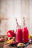 Pomegranate drink on a wooden background. Selective focus.