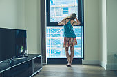 Young woman looking out window of apartment