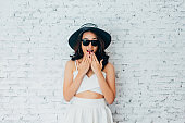 Young woman giving surprise look with fashionable sunglasses and summer hat over white wall background