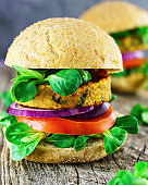 Fresh vegan sandwich with bread ciabatta onion, tomatoes, lettuce, beans cutlets on wooden background.
