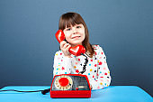 Happy 5 years old girl talking on old red telephone